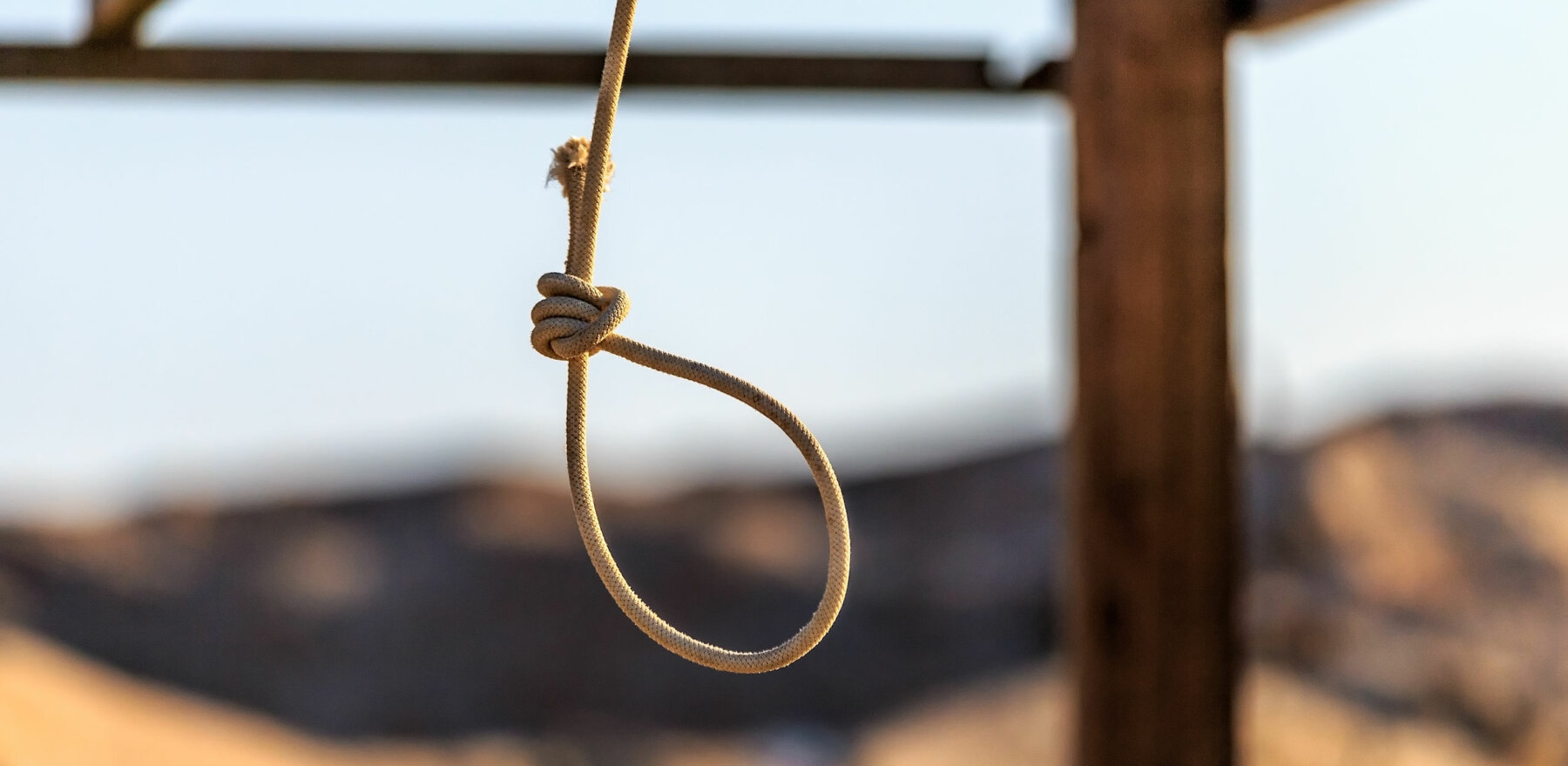Rope noose hanging outdoors in sandy wilderness on sunny blue sky background. Scaffold for committing death punisment executions or suicide abstract idea. Judgment and justice.