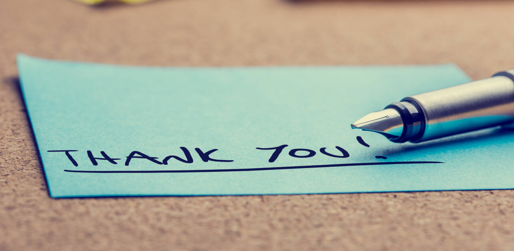 Handwritten Thank You note written on a blue sticky note lying on a cork board with a fountain pen viewed low angle.