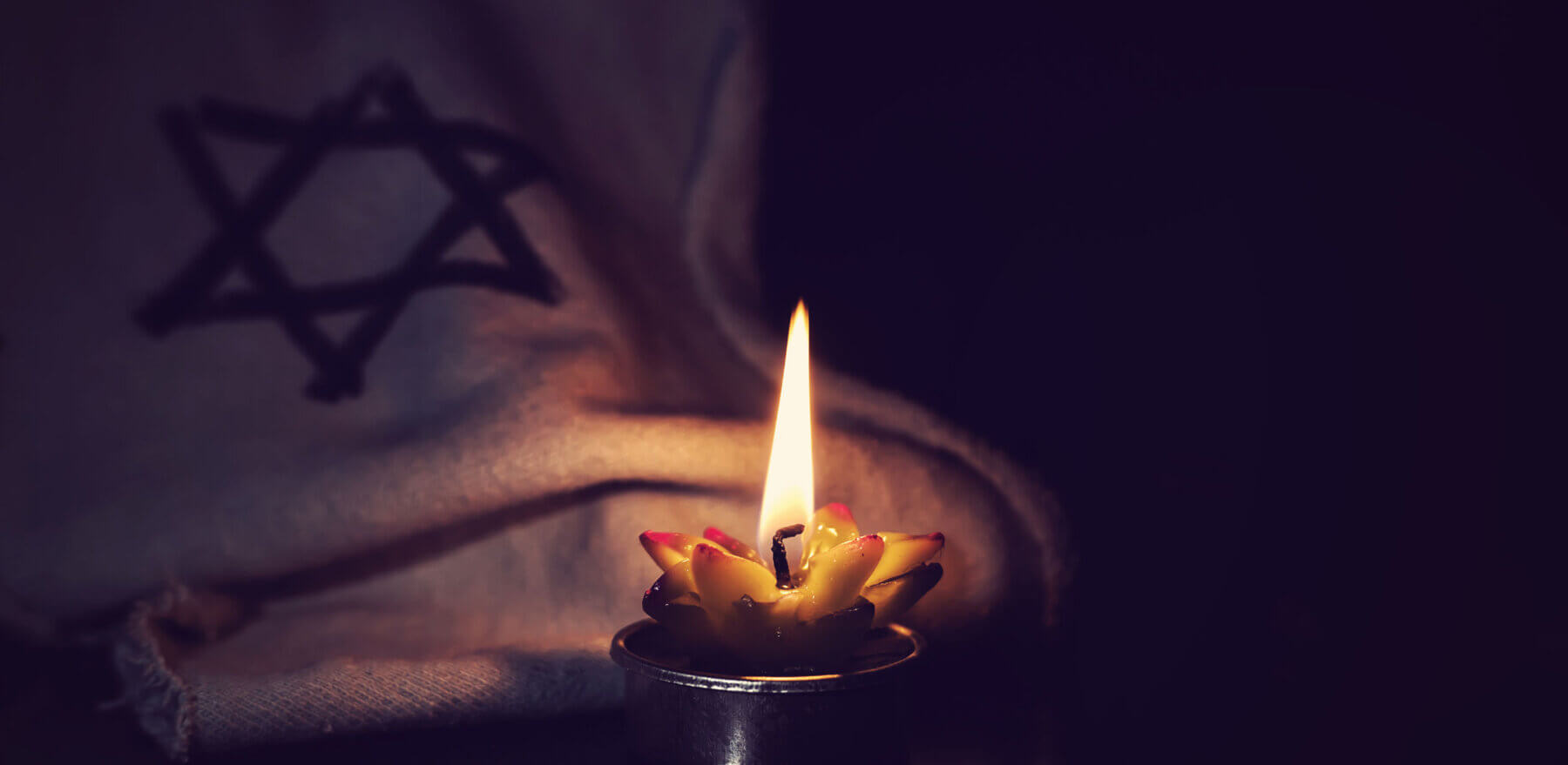 The star of David and candle stands on the table on a black background in memory of the victims of the Holocaust and genocide.