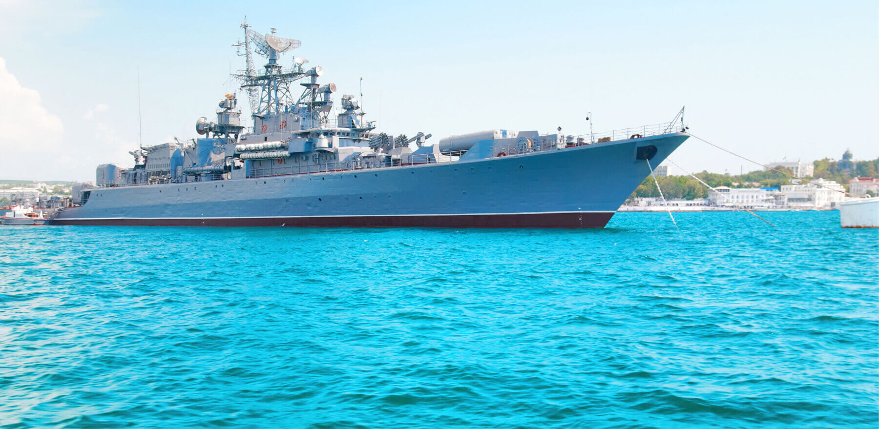 Military navy ship in blue sea with sky and clouds
